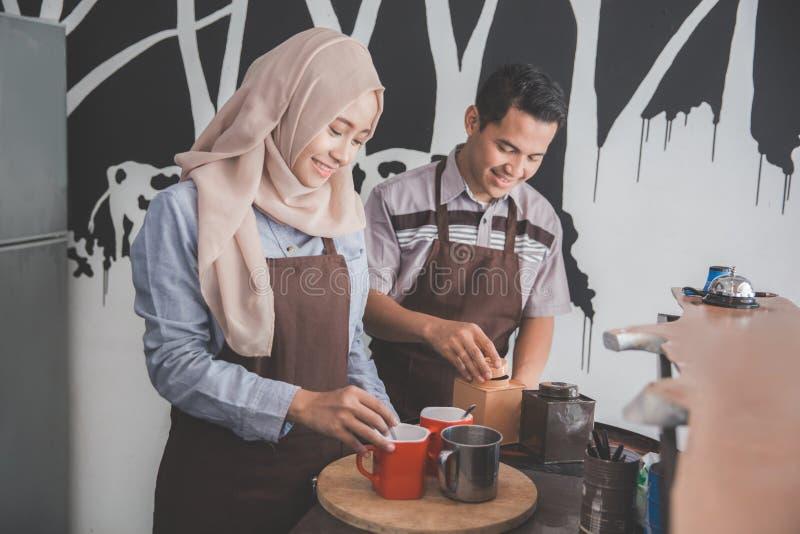Empregada de mesa fêmea e masculina asiática nova na cafetaria imagem de stock