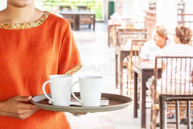 Empregada de mesa fêmea que guarda uma bandeja de copos de café no interior de um restaurante do ar livre do verão Praia de Khao  fotos de stock