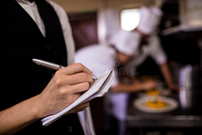 Empregada de mesa fêmea que nota uma ordem no bloco de notas na cozinha fotos de stock royalty free