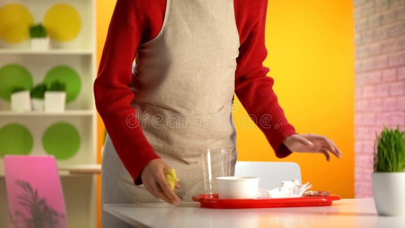 Empregada de mesa f?mea que toma a bandeja pl?stica da tabela, limpando ap?s a refei??o do cliente imagem de stock royalty free