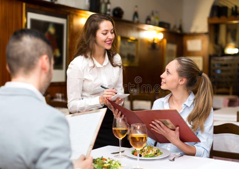 Empregada de mesa hospitaleiro que toma a ordem imagem de stock