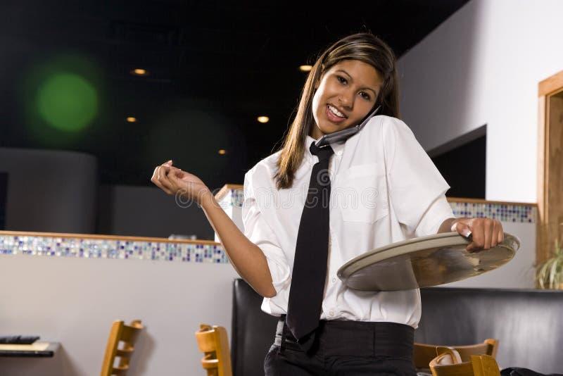 Empregada de mesa latino-americano nova no telefone de pilha fotografia de stock