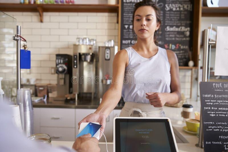 Empregada de mesa na cafetaria que toma o pagamento do cartão de um cliente imagem de stock