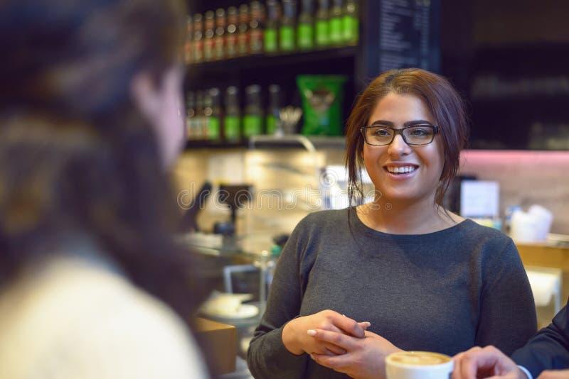Empregada de mesa nova que serve uma xícara de café fotografia de stock royalty free