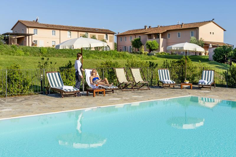 A empregada de mesa nova serve um cocktail da piscina a um cliente que senta-se em um vadio em um recurso no campo de Pisa, Itáli foto de stock