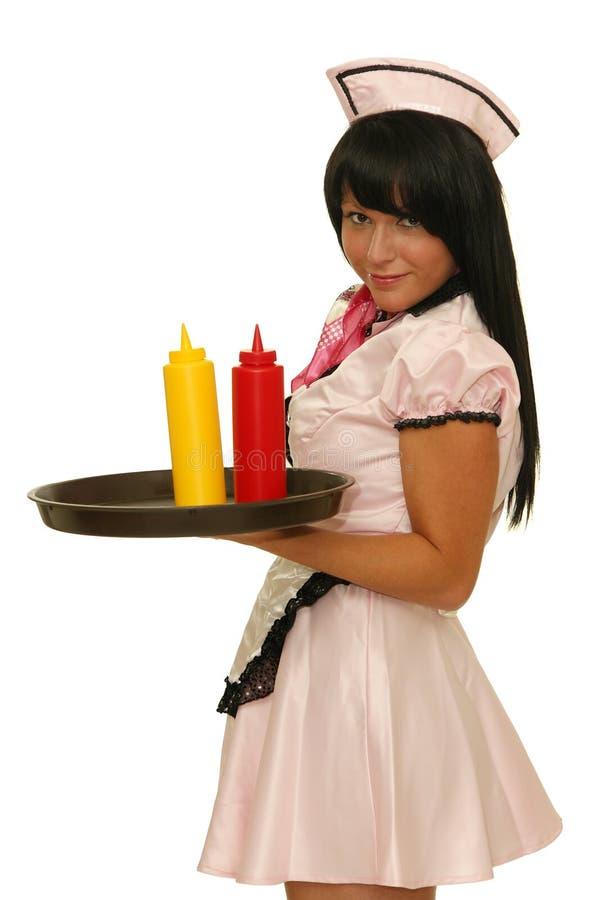 Empregada de mesa que guarda a bandeja com as garrafas da ketchup e da mostarda imagem de stock