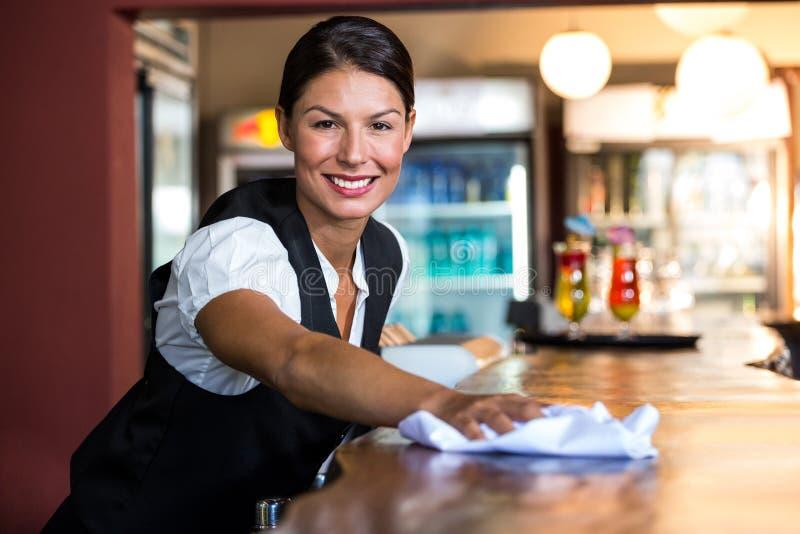 Empregada de mesa que limpa o contador imagens de stock