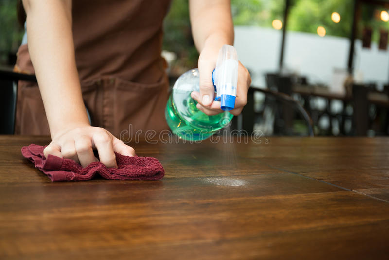 Empregada de mesa que limpa a tabela com o desinfetante do pulverizador imagem de stock royalty free