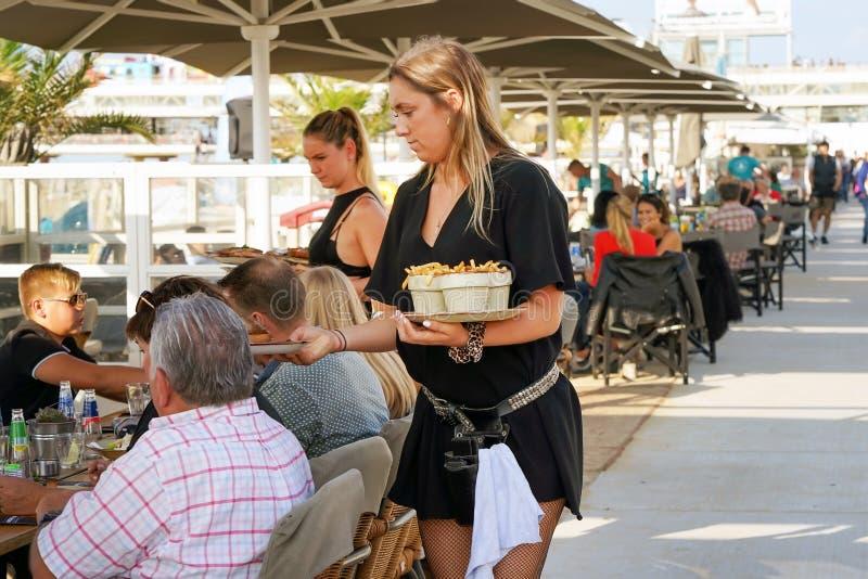 Empregada de mesa que serve um cliente no restaurante, café, barra da praia imagem de stock
