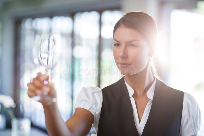 Empregada de mesa que sustenta um vidro de vinho vazio ilustração do vetor