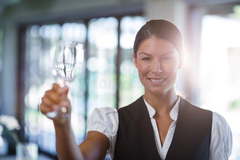 Empregada de mesa que sustenta um vidro de vinho vazio imagens de stock royalty free