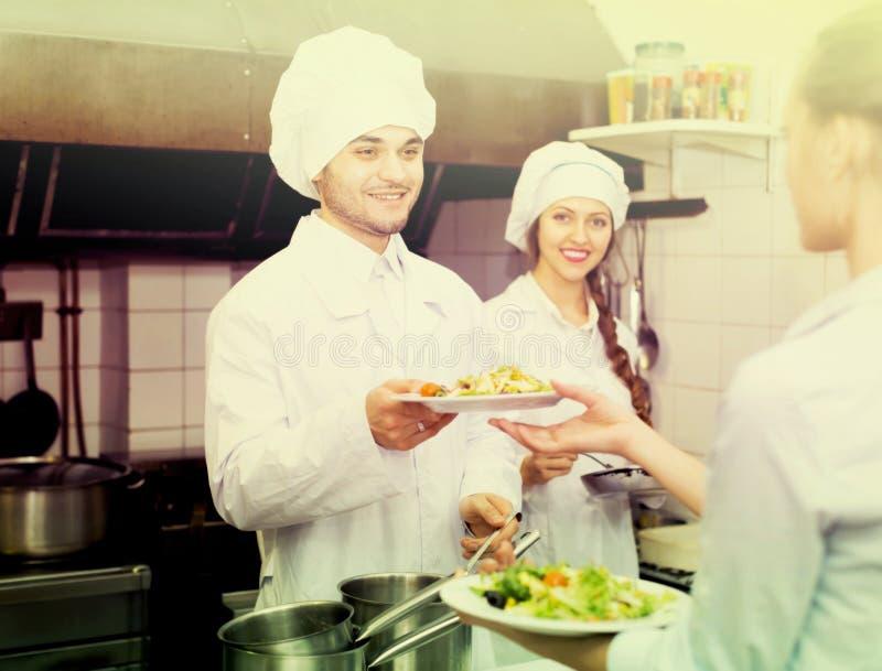 Empregada de mesa que toma o prato da cozinha fotografia de stock royalty free