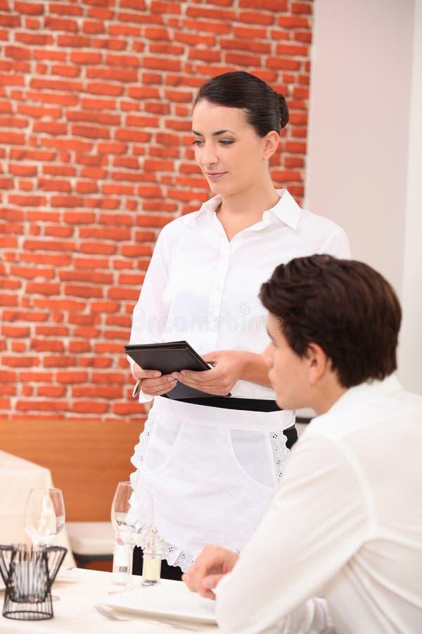 Empregada de mesa que toma uma ordem fotografia de stock