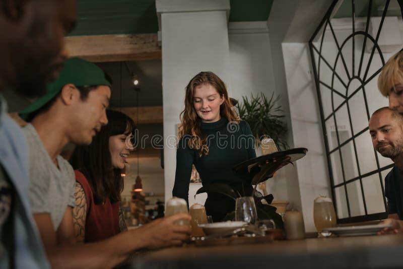 Empregada de mesa que traz a clientes bebidas em uma barra na noite fotos de stock