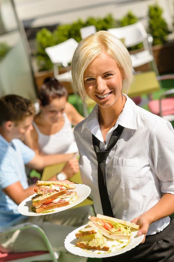 Empregada de mesa que traz sanduíches no almoço fresco das placas fotografia de stock