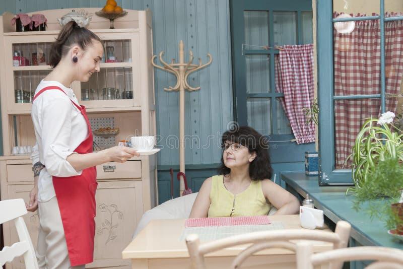 A empregada de mesa serve um visitante a um café imagem de stock royalty free