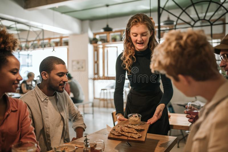 Empregada de mesa de sorriso que traz o alimento a uma tabela dos clientes foto de stock