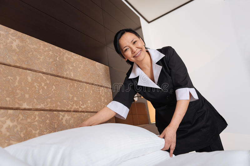 Empregada doméstica asiática alegre do hotel que faz o serviço de sala fotos de stock