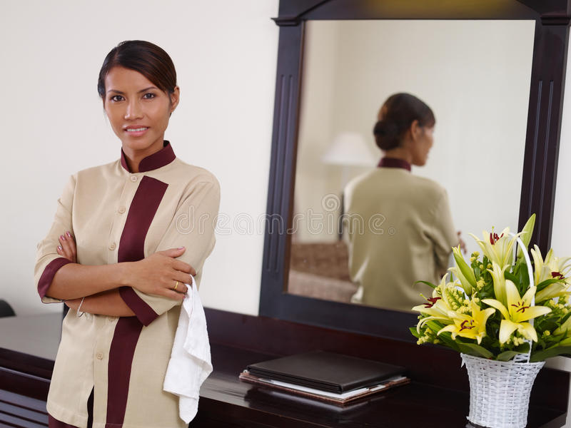 Empregada doméstica asiática que trabalha no quarto e no sorriso de hotel foto de stock