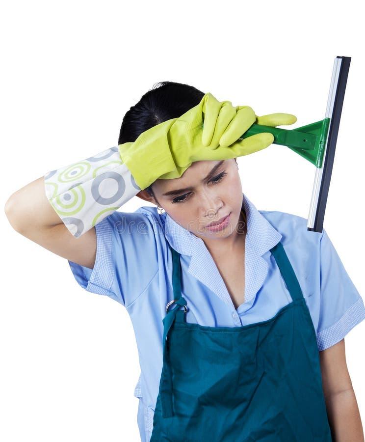 Empregada doméstica cansado que guarda a ferramenta da limpeza fotografia de stock royalty free