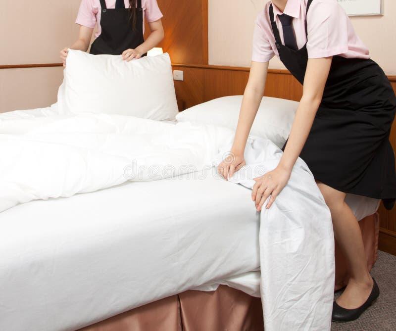 Empregada doméstica das mulheres que faz a cama no quarto de hotel fotografia de stock royalty free