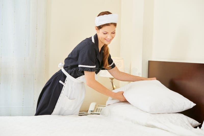 Empregada doméstica do hotel que faz a cama na sala de hotel fotos de stock