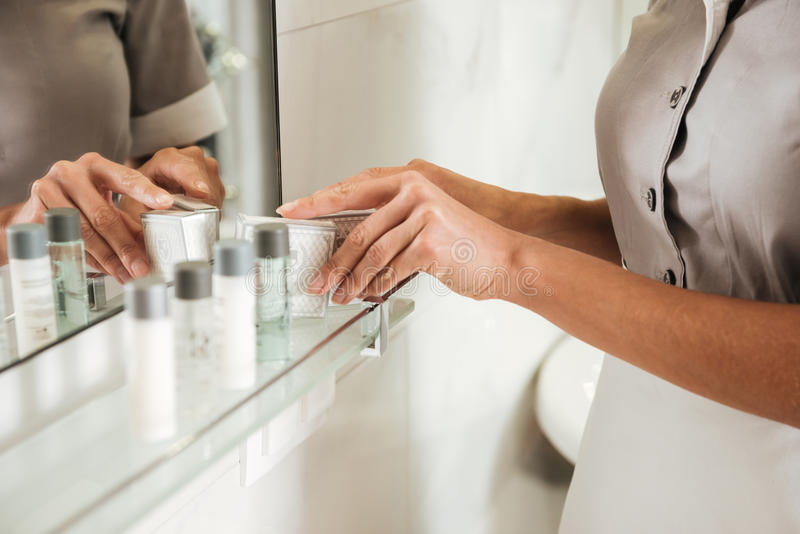 Empregada doméstica nova do hotel que põe acessórios do banho em um banheiro imagens de stock royalty free