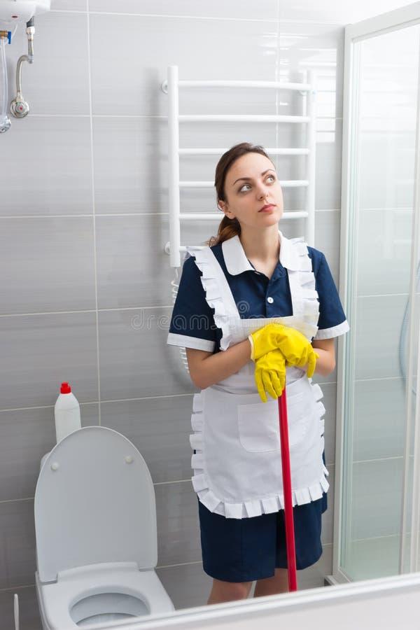 Empregada doméstica nova pensativa que toma uma ruptura de seu trabalho fotografia de stock