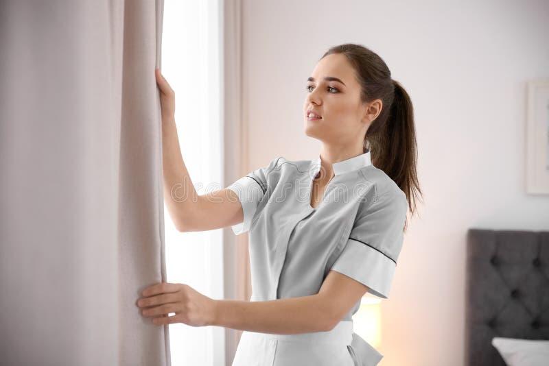 Empregada doméstica nova que ajusta cortinas fotografia de stock royalty free