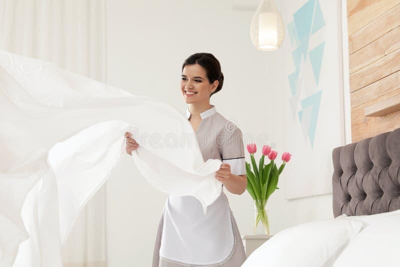 Empregada doméstica nova que faz a cama foto de stock