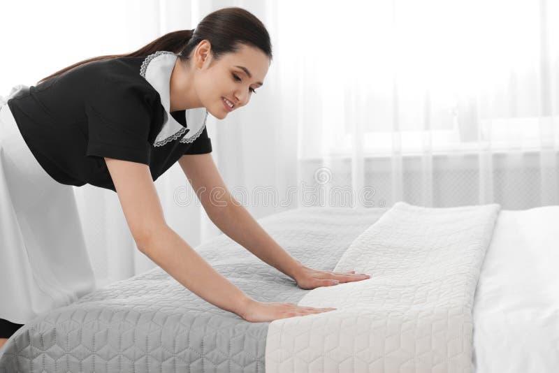 Empregada doméstica nova que faz a cama na sala de hotel fotografia de stock royalty free