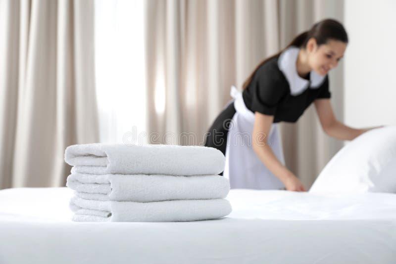 Empregada doméstica nova que faz a cama na sala de hotel, foco na pilha imagens de stock royalty free