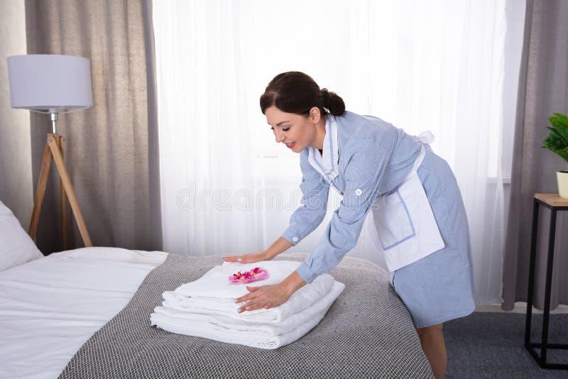 Empregada dom?stica que coloca flores na pilha de toalhas foto de stock