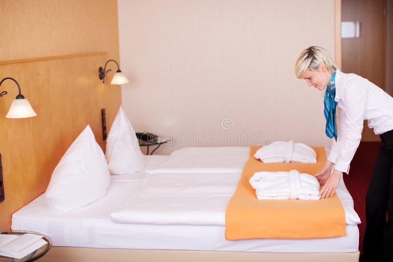 Empregada doméstica que faz a cama na sala de hotel imagens de stock royalty free