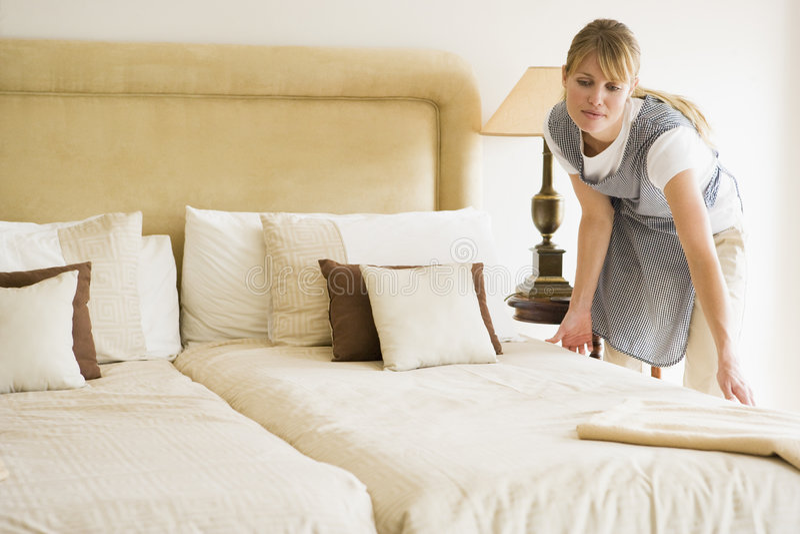 Empregada doméstica que faz a cama no quarto de hotel imagem de stock
