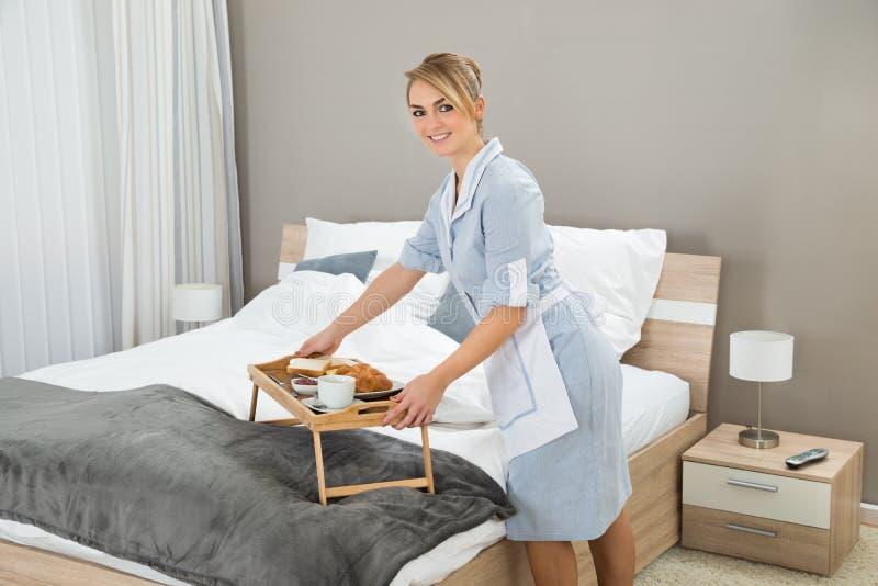 Empregada doméstica que mantém o café da manhã na sala de hotel fotos de stock royalty free