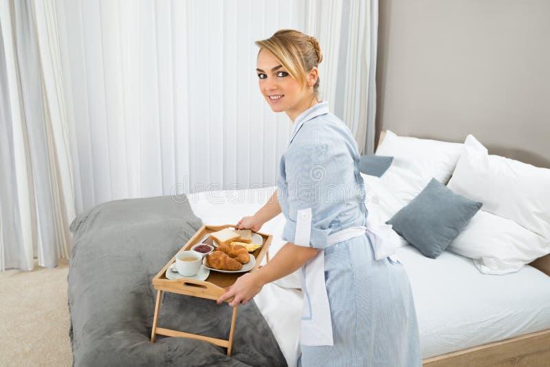 Empregada doméstica que mantém o café da manhã na sala de hotel imagens de stock royalty free