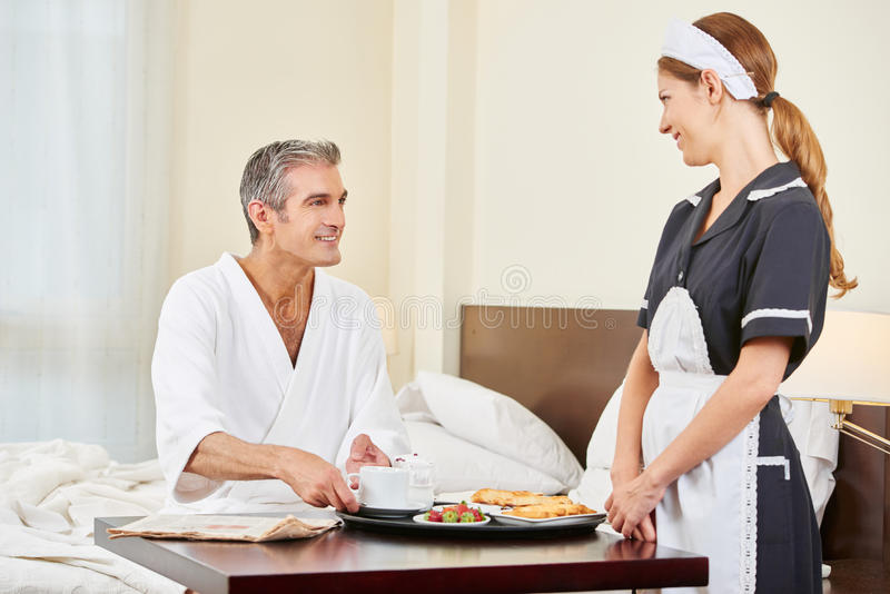Empregada doméstica que traz o café da manhã como o serviço de sala foto de stock royalty free