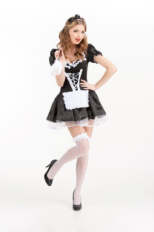 Empregada doméstica 'sexy'. Empregada doméstica nova bonita na meia-calça branca que guardara a escova imagens de stock royalty free