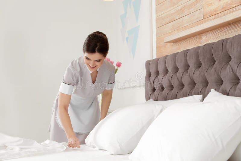 Empregada dom?stica nova que faz a cama na sala foto de stock royalty free