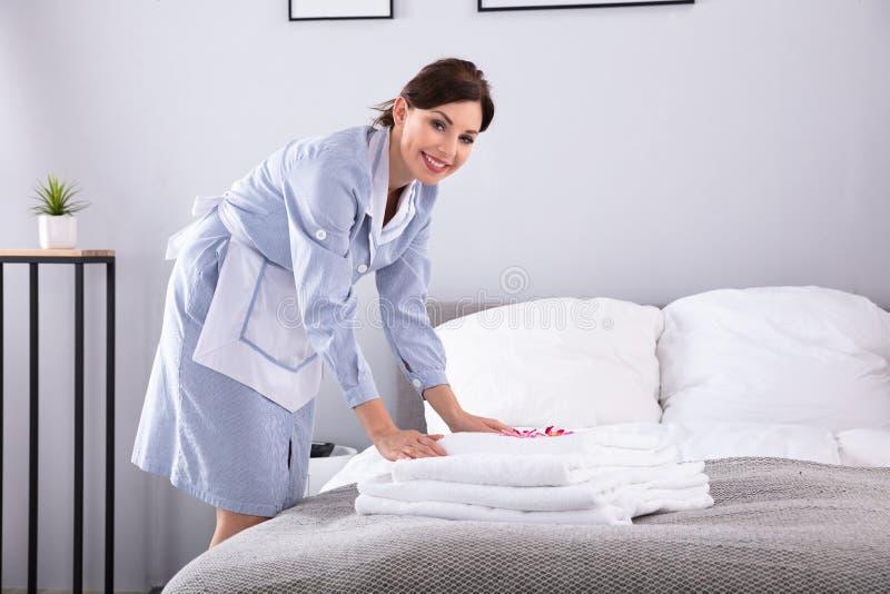Empregada dom?stica que coloca flores na pilha de toalhas imagem de stock royalty free