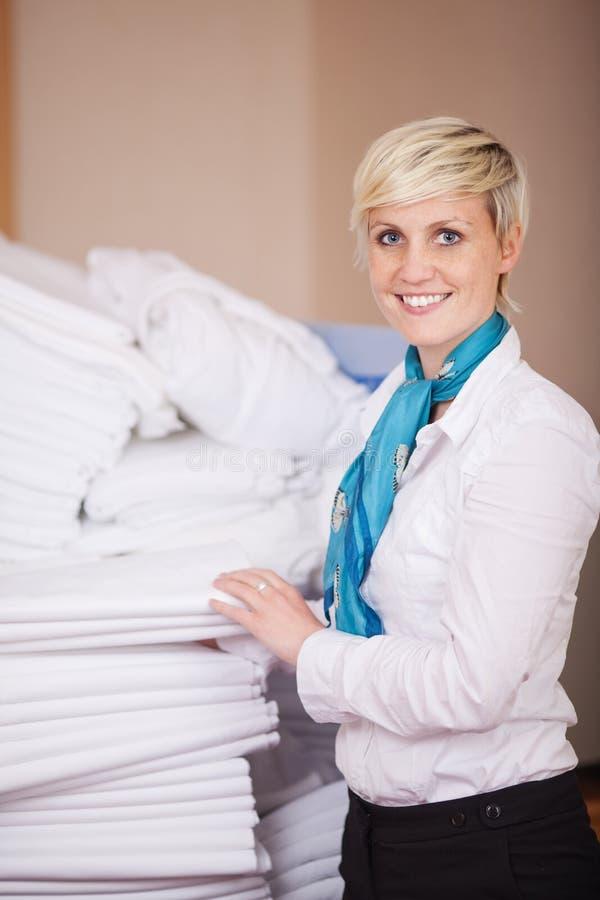 Empregada fêmea que empilha folhas na sala conservada em estoque foto de stock