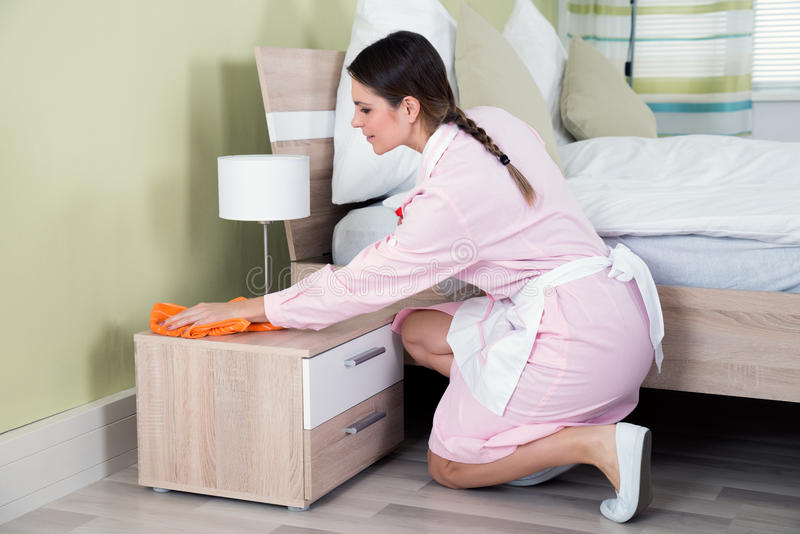 Empregada fêmea que limpa Nightstand fotografia de stock