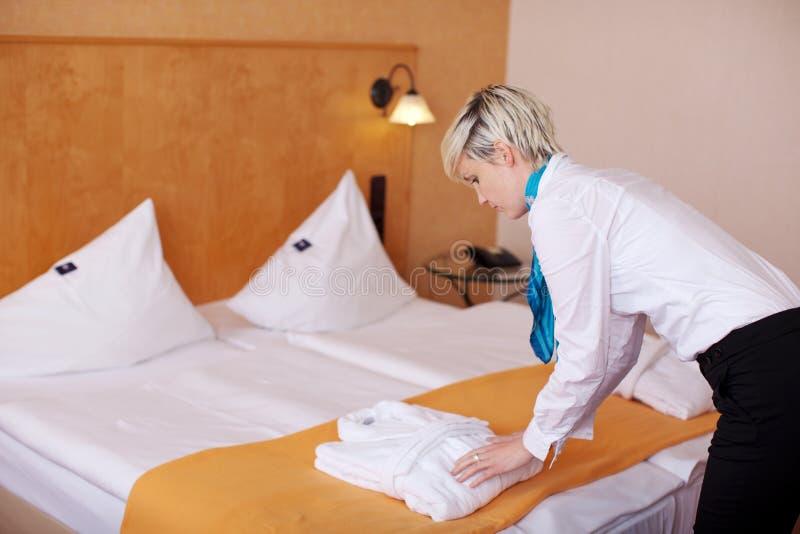 Empregada fêmea que mantem o roupão na cama fotografia de stock