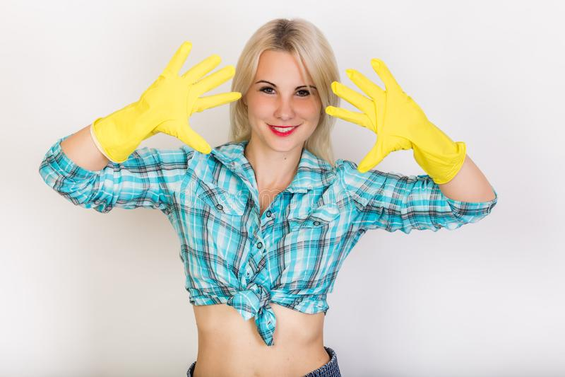 Empregada loura de sorriso feliz em luvas de borracha amarelas imagens de stock royalty free