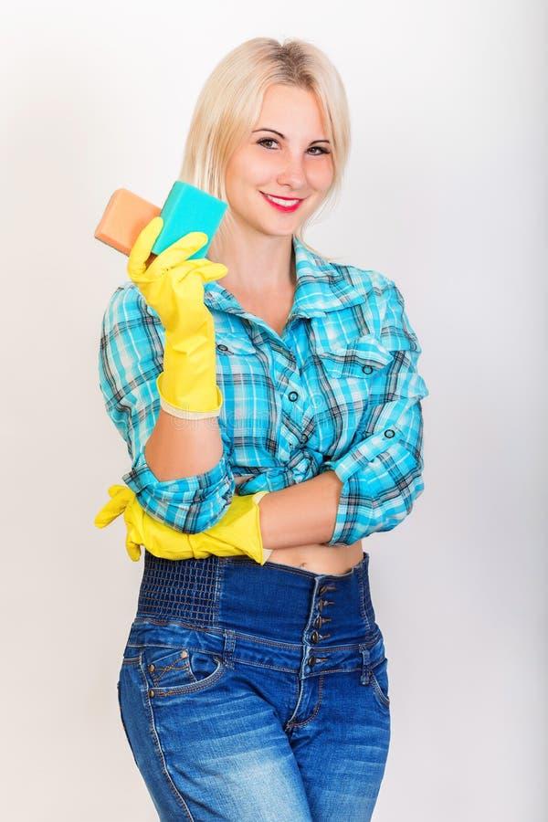 A empregada loura feliz demonstra esponjas para lavar imagem de stock