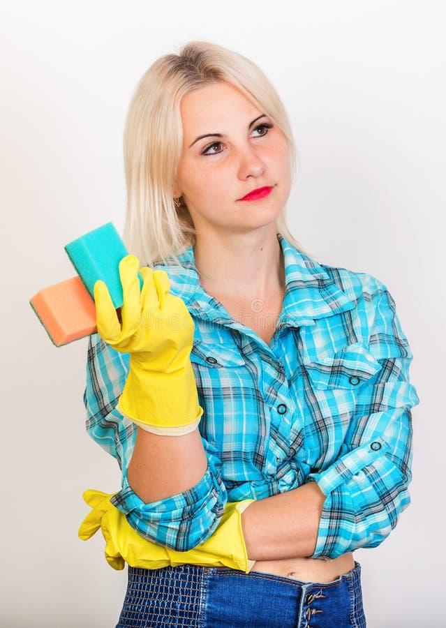 A empregada loura pensativa demonstra esponjas para lavar foto de stock