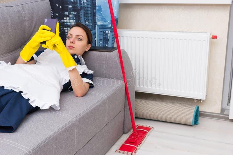 Empregada ou empregada doméstica preguiçosa que relaxam no trabalho imagem de stock royalty free