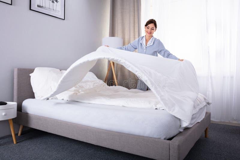 Empregada que arranja o Bedsheet na cama imagens de stock