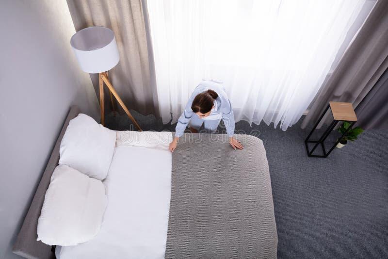 Empregada que faz a cama na sala de hotel imagem de stock